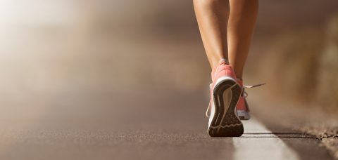 Running shoe closeup of woman running on road with sports shoes
